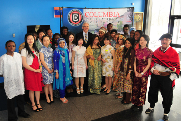 A group of diverse students and staff dressed in their culture's traditional clothing.