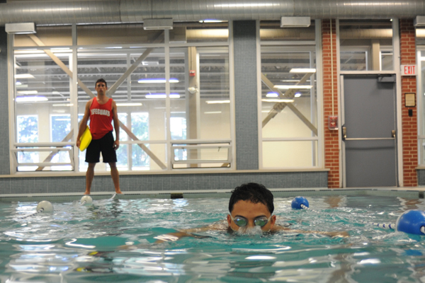A student swimming in an indoor pool as a lifeguard watches.