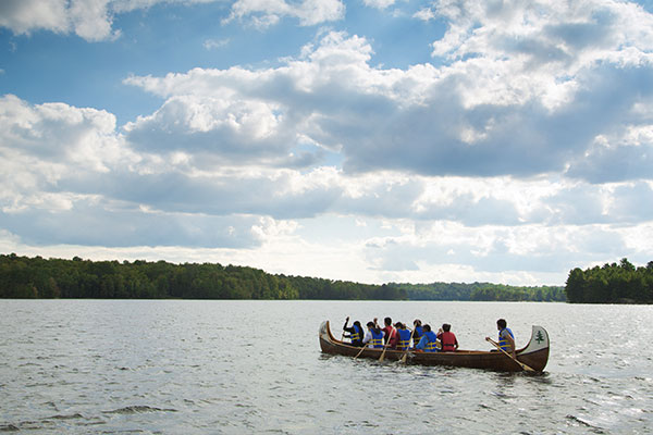 A group of students canoeing on a lake under a blue cloudy sky.